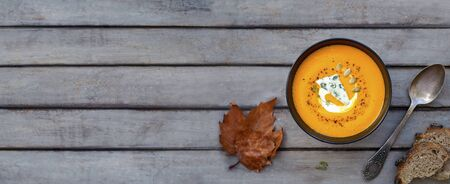 Hot pumpkin soup with blue cheese, herbs and multi-cereal bread on a wooden table. View from above Reklamní fotografie