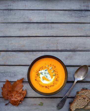 Hot pumpkin soup with blue cheese, herbs and multi-cereal bread on a wooden table with your text on top. View from above Reklamní fotografie