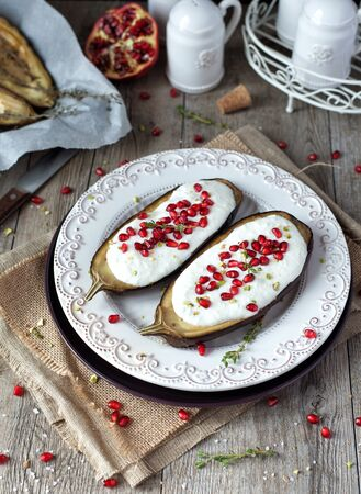 Roasted eggplants with yogurt sauce and pomegranate seeds on a rustic table.