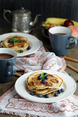 Banana pancakes with blueberry on a rustic served table