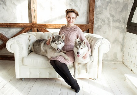 Young beautiful pregnant woman with husky on a sofa