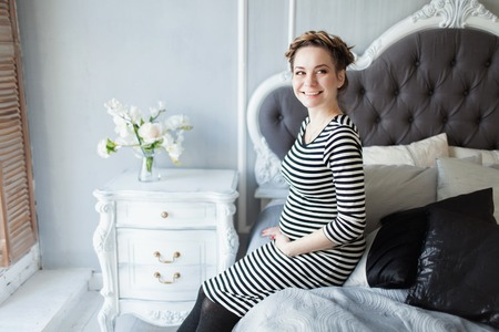 Young beautiful pregnant woman in a french striped dress sitting on the bed smiling.