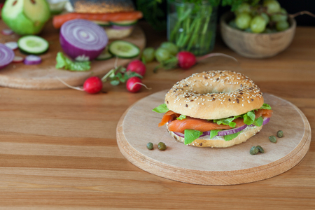 Bagel with smoked salmon on a wooden board Reklamní fotografie