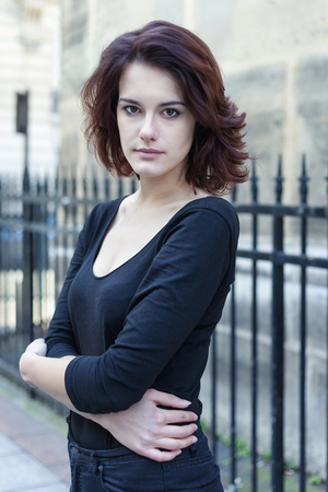 Beautiful young girl with dark hair in the street. Reklamní fotografie