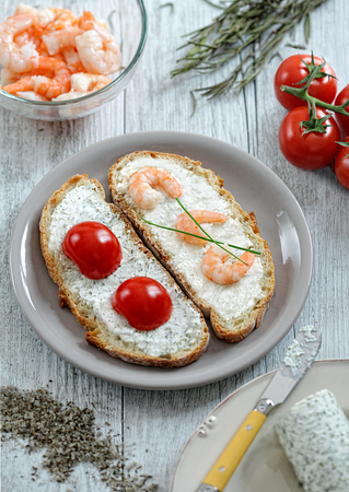 Two open sandwiches with tomatoes and shrimps on a white wooden table