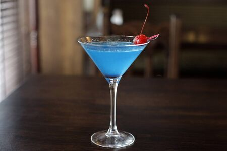 A blue cocktail in a triangle glass on a dark rustic wooden table. Reklamní fotografie