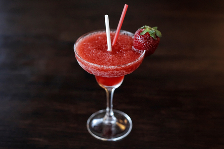 Strawberry Daiquiri cocktail in a triangle glass on a dark rustic wooden table