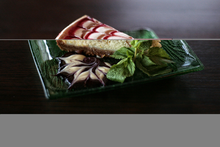 A strawberry cheesecake on a plate with a leaf of mint on a rustic wooden table. Reklamní fotografie