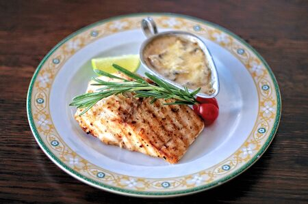 A plate of grilled escolar fish with creamy sauce on a rustic wooden table.