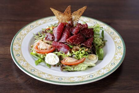 A plate of a salad with beef jerky on rustic wooden table. Reklamní fotografie