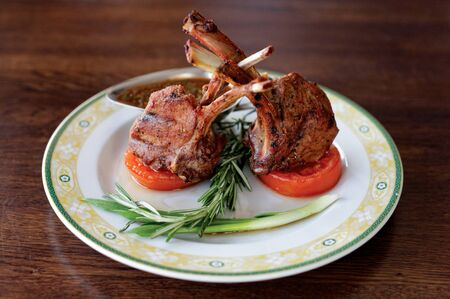 Grilled rack of lamb on a plate that is on rustic table.
