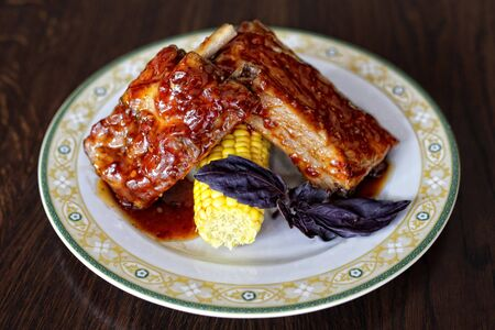 Caramelized pork ribs with corn on a plate with rustic wooden background.