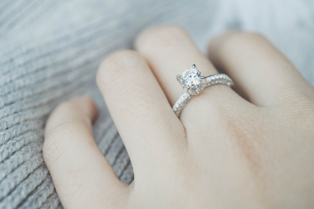 Close up Diamond ring on womans finger before wedding with white scarf background.(soft and selective focus)