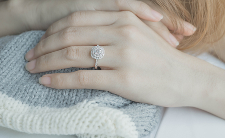jewellry: Close up Diamond ring on womans finger before wedding with white and gray scarf background.soft sunlight tone(soft and selective focus)Close up of elegant diamond ring on the finger with gray Scarf Stock Photo