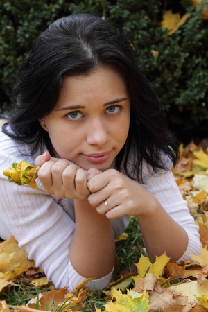 Beautiful, thoughtful girl with the rose of maple leaves
