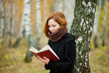 portrait of beautiful girl reading in the autumn park photo