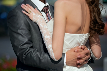 Close up Grooms hand on Brides back photo