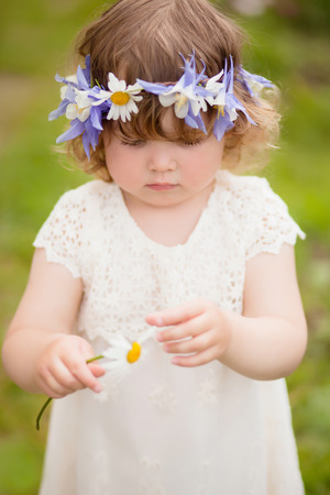 vertical natural light photo of a little girl guessing on a flower in ? sunny sammer day