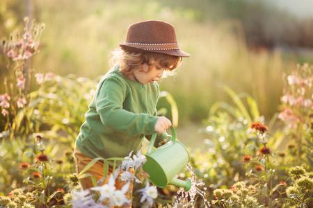 Composizione orizzontale del tramonto di regolazione di un bambino di innaffiatura dei fiori della ragazza nel giardino Archivio Fotografico