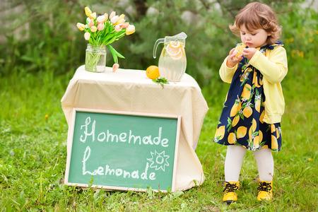 Horizontale natuurlijke lichtfoto van een klein meisje met limonadestand