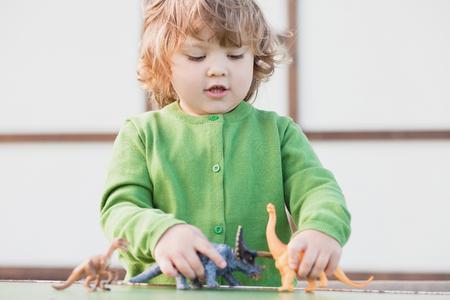 peuter jongen plezier spelen met een stuk speelgoed dinosaurus, horizontale daglicht foto