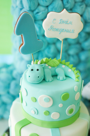 Blue and green first year birthday cake with cute dragon and russian text, for little boy. Vertical photo