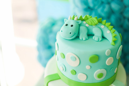 Blue and green first year birthday cake with cute dragon, for little boy.  Фото со стока
