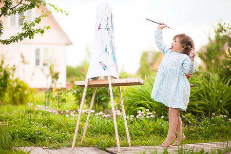 Cute toddler girl painting on the easel in the garden and having fun. Talented kids. Early art education.