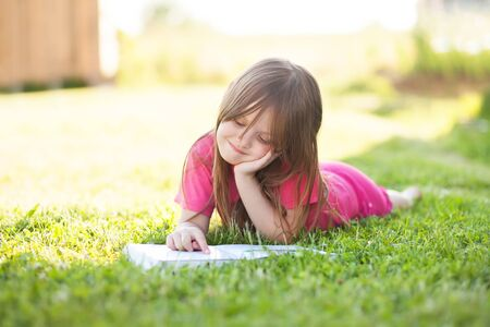 learning by doing: Summer reading. Adorable little girl lying on the grass outdoors reading a book, learning, doing homewark.