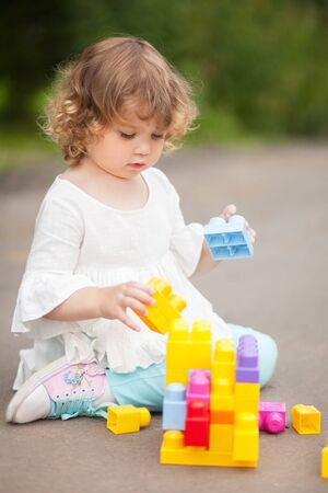 Adorable little girl play with color plastic block, building and having fun. playing with educational toys. early developement