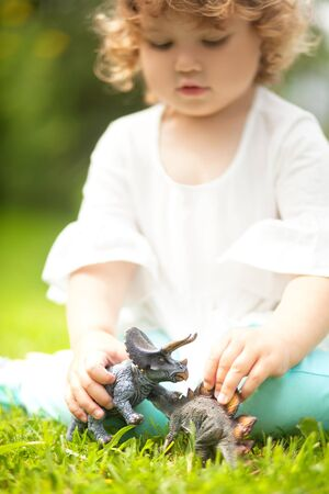 peuter jongen plezier spelen met een stuk speelgoed dinosaurus, zittend op een groen gras. verticale natuurlijke lichtfoto. zonnige zomerdag. jongensspeeltjes voor een klein meisje