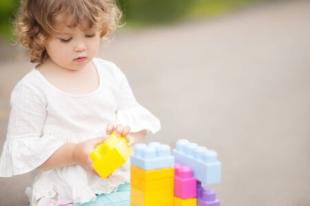 Adorable little girl play with color plastic block, building and having fun. playing with educational toys. early developement. empty place for text Stock Photo
