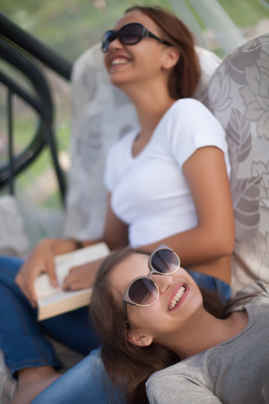 tine: Best friends spending tine together in summer day. Wearing sunglasses, smilimg, reading. Doing homework, lerning.