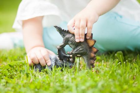 peuter meisje plezier spelen met een stuk speelgoed dinosaurus, zittend op een groen gras, zonnige zomerdag. dino gevecht