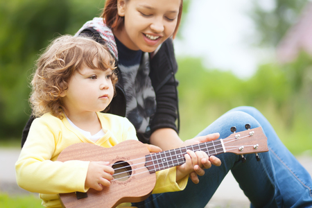 teching: Young attractive nanny teachs little girl playing ukulele, sunny day, outdoors. Early music education. babysitting. elder sister. young mother