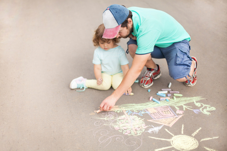 Caring loving father, happy family. Single parent, single father. Drawing with color chalk. Sunny summer days. Happy childhood. Preschooler leisure time. Kids spending time with parents. Artistic talented kids. Colorful chalk drawing. Children's drawings. Standard-Bild