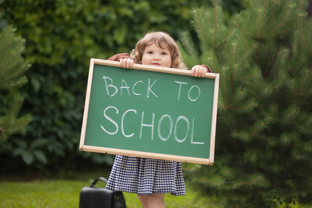 Cute caucasian little girl holding chalkboard written back to school Stock Photo