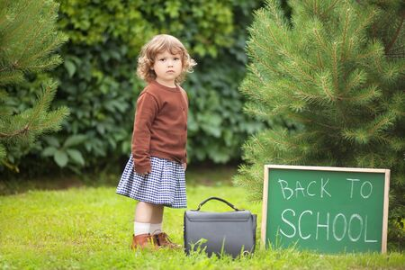Caucasian toddler child kid girl looking with serious face, back to school. Fall outdoors, autumn day, education concept, back to school concept. Early developement, early education. back to school written on chalk blackboard.