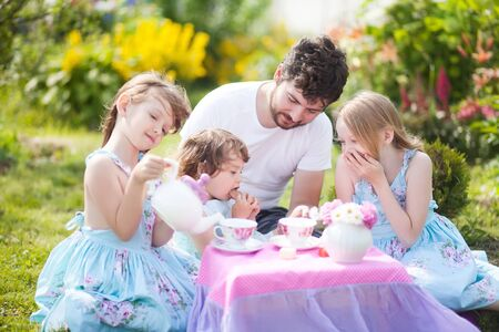 sitter: Father playing tea party game with his three adorable daughters. Having many children single father. Loving and caring father. Single parent. Beautiful decorated tea party outdoors, at the backyard. male babysitter, sitter, childminder, sitter-in