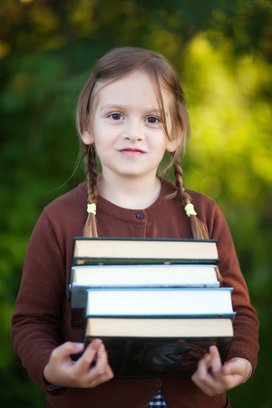 first year student: Adorable happy little preschooler girl with pigtails ready back to school, holding pile of textbooks, school books, manuals.  Wearing school uniform. Warm september fall day. Smart clever intellegent little girl. Stock Photo