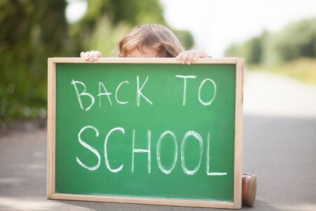 Adorable little girl hiding behind the chalkboard, dont want back to school.