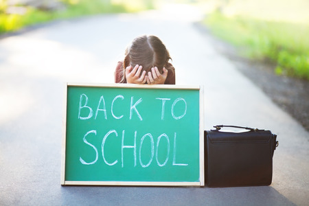 Depressed little girl hiding behind the chalkboard amd crying, dont want back to school. Have promlems with schoolmates or teathers. Stressed outsider kid. Teathers pressure consept. Negative feelings, fear of school. Stock Photo