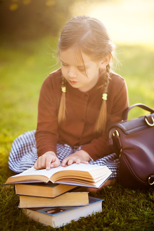 Adorable happy little preschooler girl with pigtails ready back to school, reading textbooks outdoors, school books, manuals.  Wearing school uniform. Warm september fall day. Smart clever intellegent little girl. Zdjęcie Seryjne