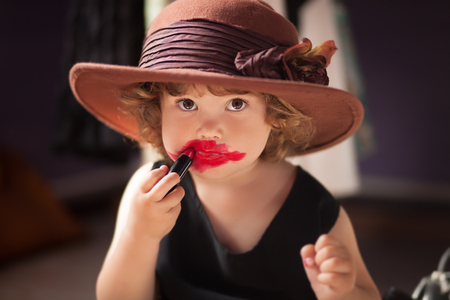 Little girl making makeup with mother cosmetics. Learning to be a woman 스톡 콘텐츠