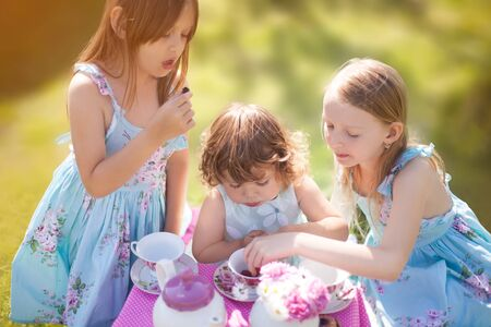 Adorable three little sisters girls dressed like princesses playing tea party. Beautiful decorated tea party outdoors, at the backyard. Stock Photo