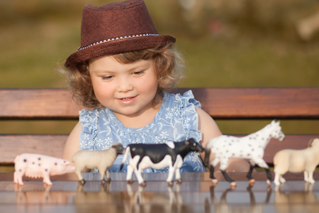 Cute toddler girl playing with farm animal figures outdoors. Summer leisure. childhood on countryside. Child learning farm animals. Early education and developement. Role-playing with plastic animals