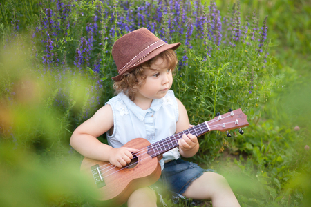 Music education, little musician, art school. Toddler girl play ukulele guitar