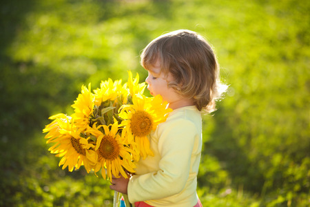 Sunny day, summer vacation. cute little girl with yellow sunflowers, outdoor portrait