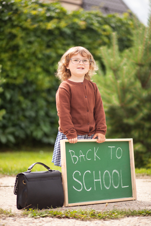 Cute toddler girl wearing glasses and school uniform with back to school blackboard. fall outdoors, education concept, sunny autumn day. early education, little genius, Wunderkind concept.