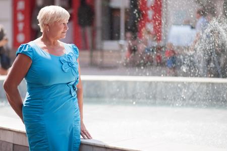 Een elegante oudere vrouw die buitenshuis.